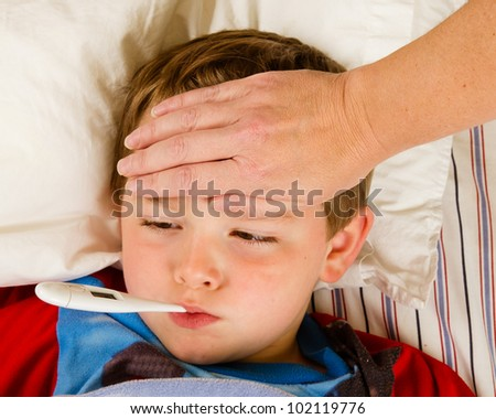 Sick child boy being checked for fever and illness while resting in bed - stock photo