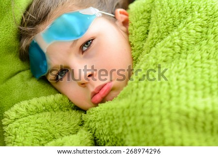 Sick child girl. Sick sad little girl under a blanket with a cooling compress on her forehead - stock photo