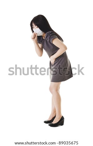 Sick Chinese woman wearing a face mask holds her stomach and coughs. - stock photo