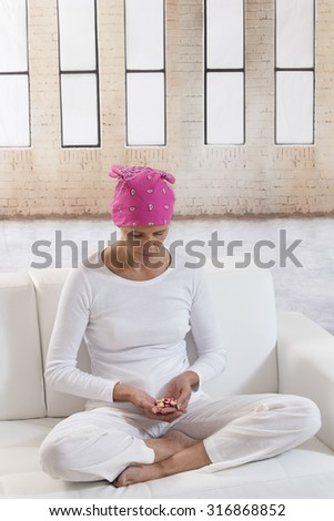 Sick depressed woman wearing headscarf  looking down with drugs on a coach