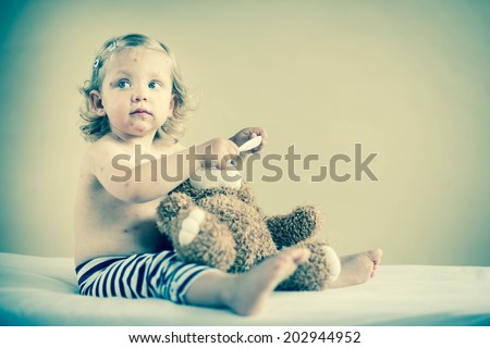 Sick girl is sitting on the bed with teddy-bear - stock photo