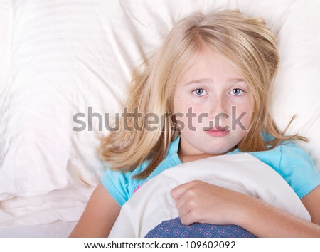 sick girl laying in bed with a sad look - stock photo