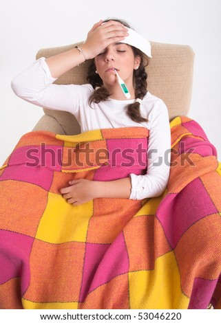 Sick girl sitting on an armchair, covered with a blanket, a compres on her forehead, holding a thermometer in her mouth - stock photo