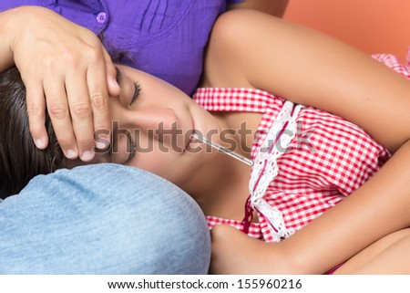 Sick girl suffering a fever with a thermometer in her mouth and her mother checking her temperature - stock photo