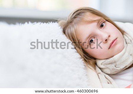 Sick girl with scarf looking at camera