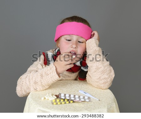Sick in headband girl sits near table with medicine and take pill on gray background - Treatment, cold or disease concept - stock photo