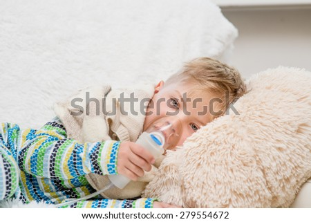 sick little boy makes inhalation home - stock photo