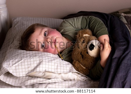sick little boy with bright red cheeks and thermometer in mouth, hugs his teddy bear in bed - stock photo