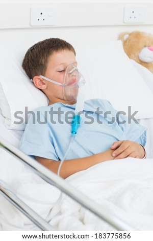 Sick little boy with oxygen mask in hospital ward