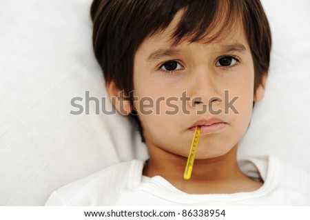 Sick little boy with thermometer, laying on bed - stock photo