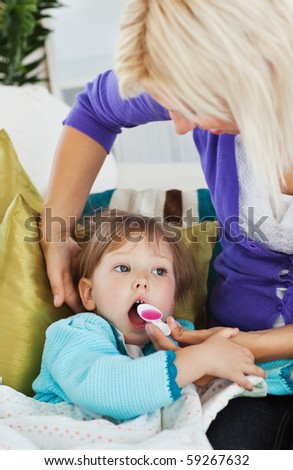Sick little girl getting syrup from her caring mother at home - stock photo