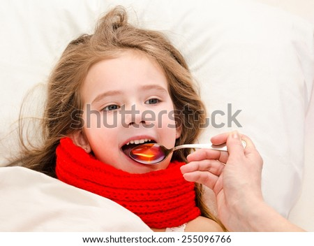 Sick little girl in bed taking medicine with spoon - stock photo