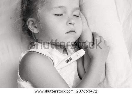 Sick little girl in bed with a thermometer ( black and white ) - stock photo