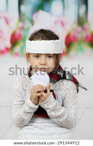 Sick little girl in headband with very big pill in hands - stock photo