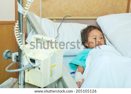 Sick little girl in hospital bed - stock photo