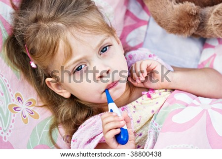 Sick little girl is having her temperature taken. - stock photo
