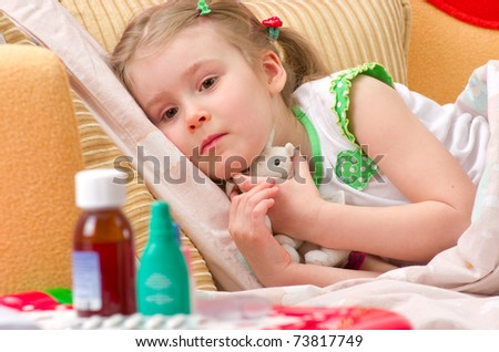 Sick little girl lying in her bed at home looking on pills - stock photo
