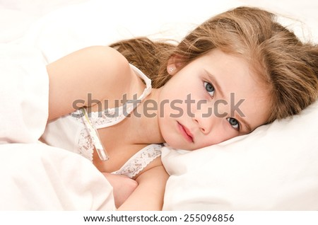 Sick little girl lying in the bed with thermometer