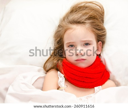Sick little girl lying in the bed with thermometer - stock photo