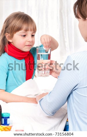 Sick little girl sitting on bed with her mother or doctor - stock photo