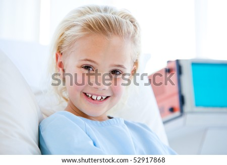 Sick little girl smiling at the camera sitting on a hospital bed - stock photo