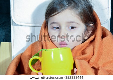 Sick little girl with blanket and cup. Sick child with chapped lips. Little girl with flu drinking her medicine.  - stock photo