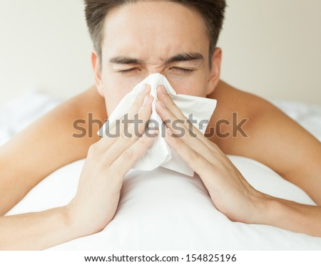 Sick man. Flu. Sneezing into tissue. Man caught cold. - stock photo