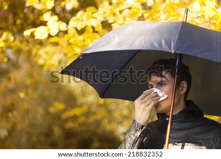 Sick man holding umbrella  and  blowing nose at autumn day - stock photo