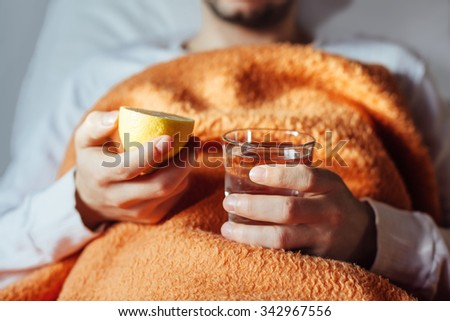 Sick man in bed with fresh glass of water and lemon - stock photo