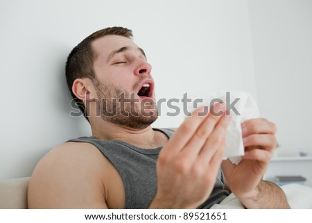 Sick man sneezing in his bedroom - stock photo