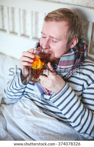 sick man with a scarf drinking hot tea in bed - stock photo