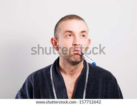 Sick man with a thermometer isolated on grey background - stock photo