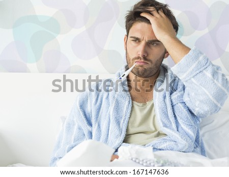 Sick man with thermometer in mouth sitting on bed at home - stock photo