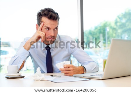 Sick man working on laptop in the office - stock photo