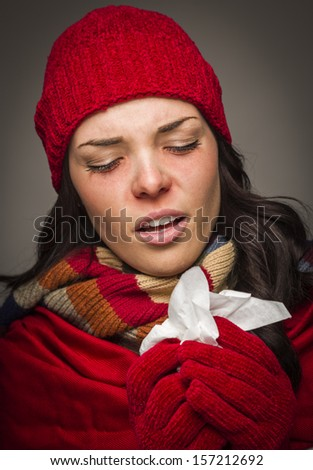 Sick Mixed Race Woman Wearing Winter Hat and Gloves Blowing Her Sore Nose with a Tissue. - stock photo