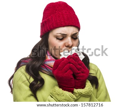 Sick Mixed Race Woman Wearing Winter Hat and Gloves Blowing Her Sore Nose with a Tissue Isolated on White Background.  - stock photo
