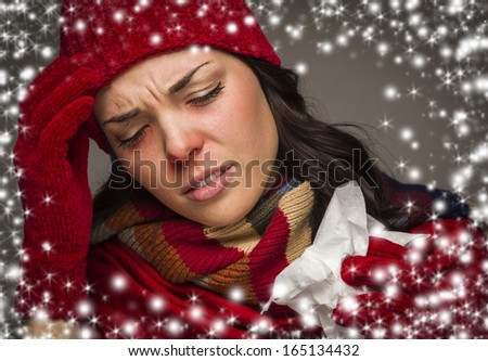 Sick Mixed Race Woman Wearing Winter Hat and Gloves  with a Tissue and Snow Effect Surrounding Her. - stock photo