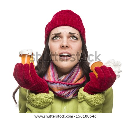 Sick Mixed Race Woman Wearing Winter Hat and Gloves with a Tissue Holding Empty Medicine Bottle Isolated on White.  - stock photo