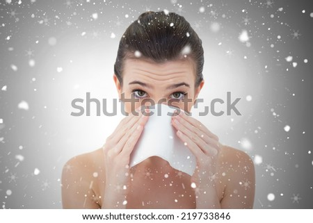 Sick natural brown haired model sneezing in a tissue against snow falling - stock photo