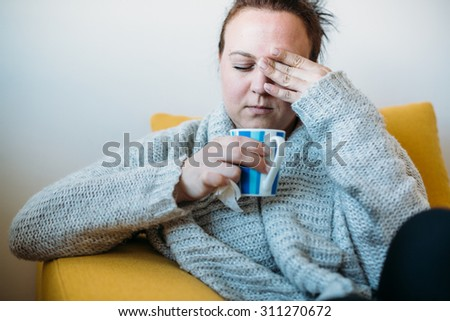 Sick Overweight woman with a headache sitting on couch - stock photo