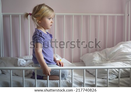 Sick sad little girl with an intravenous cannula in her hand, sitting on hospital bed  - stock photo