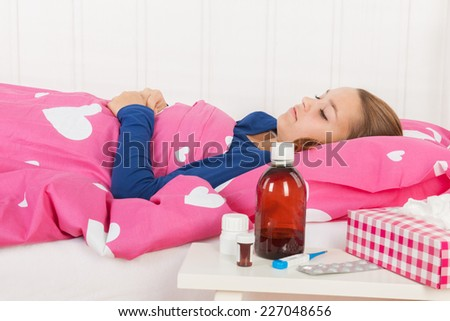 Sick teen girl laying in bed with medicine in front (focus on girl) - stock photo