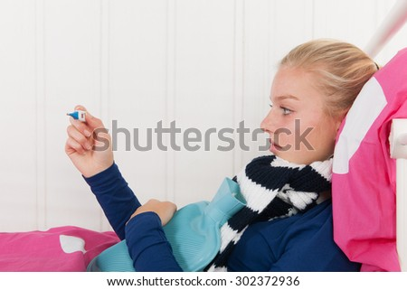 Sick teen girl laying in bed with thermometer for the temperature - stock photo