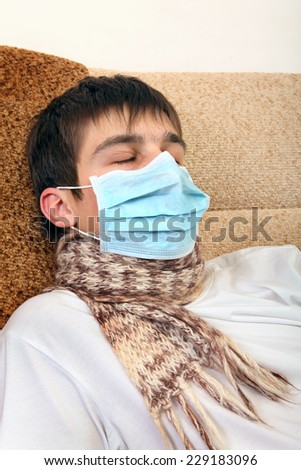 Sick Teenager in Flu Mask on the Sofa at the Home - stock photo