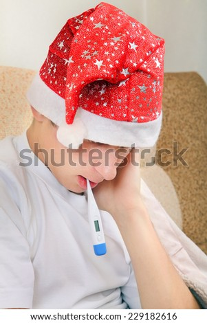 Sick Teenager in Santa Hat with Thermometer on the Sofa at the Home - stock photo