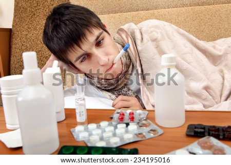 Sick Teenager on the Sofa at the Home with Pills on foreground - stock photo