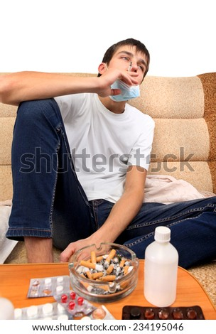 Sick Teenager smoking Cigarette on the Sofa with the Pills on foreground - stock photo