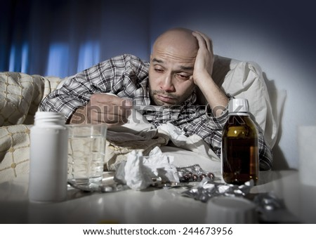 sick wasted man lying in bed wearing pajama suffering cold and winter flu virus having medicine tablets in health care concept looking temperature on thermometer - stock photo