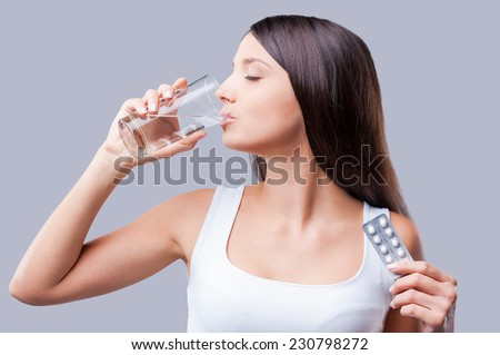 Sick woman. Beautiful young woman taking pills and keeping eyes closed  - stock photo