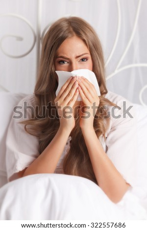 Sick woman blowing her nose in the bed - stock photo